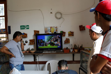 People watch a Colombian national TV broadcast with the news about Venezuela at a bar in Cucuta