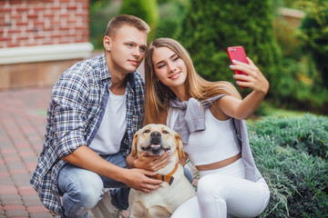 Let's make a selfie! Young happy couple with labrador make photo at the park.