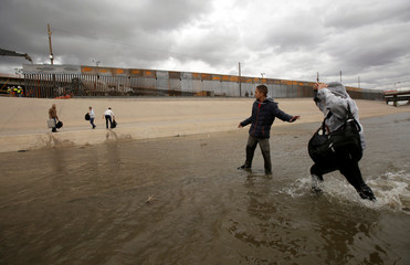 Migrants cross a river next to a section of the new wall between El Paso and Ciudad Juarez