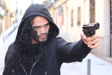 Threatening looking ethnic man holding gun