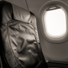 Interior of aircraft with empty seats and sunlight at the window. Travel concept. Black and white