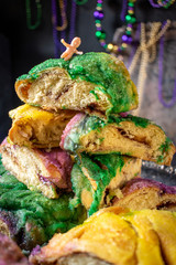 king cake with baby surrounded by mardi gras beads
