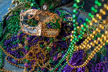 mardi gras mask and beads in green, gold, and purple