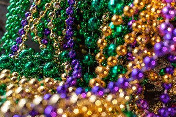 mardi gras beads with bokeh in green, gold, and purple