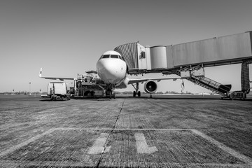 White wide body passenger aircraft with a boarding gate at the airport apron. Black and white. Airplane travel