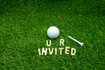 Golf invitation with golf ball and tee on green