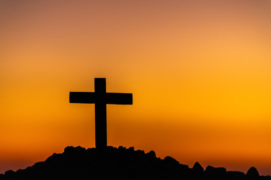 The silhouette of the cross across the mountain at sunset