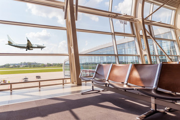 View from the airport lounge to landing aircraft, Car airfield maintenance at airport apron. Airplane travel concept Wall mural
