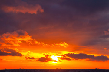 rich bright orange sun in a cloudy sky over the sea during sunset