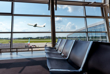 View from the airport lounge to plane taking off, passenger aircraft in the sky. Airplane travel concept