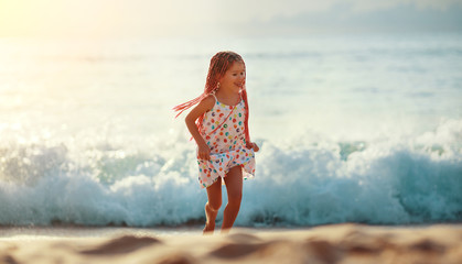 happy child girl  with flying hair dancing and runing on  beach at sunset