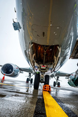 Aircraft, nose close up. Airplane maintenance and plane preparation for departure. Bad weather at airport