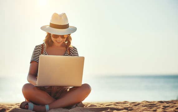 young woman working with laptop on nature in beach.