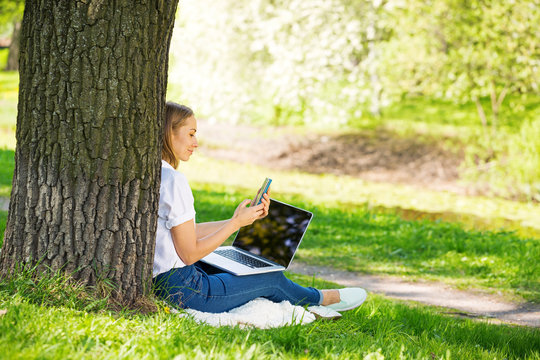 Blond girl in summer park with laptop
