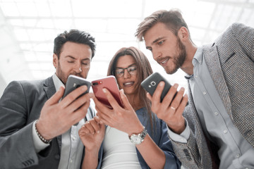 close up.business colleagues reading SMS on their smartphones