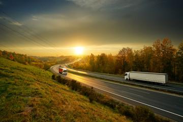 Fotobehang - Three trucks driving on the asphalt highway in autumn landscape at sunset