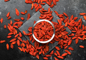 Dried red goji berries on gray background - useful and healthy food concept, flat layout with the place for text, top view