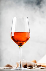 Trendy food and drink, orange wine in glass, gray table background, space for text, selective focus vertical image