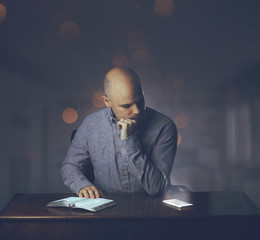 Man reading Bible and distracted
