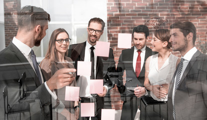 group of business people looking at notes on glass