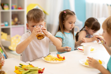 Lunch in daycare. Group of children eat healthy food. Kid boy drinking juice during dinner in kindergarten
