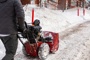 Man walking with a snowblower in winter. Close up rear view of a man walking down the sidewalk with a snowblower to clear the snow from the house's entrances after a winter storm