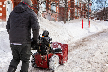 Man walking with a snowblower in winter. Rear view of a man walking down the sidewalk with a snowblower to clear the snow from the house's entrances after a winter storm