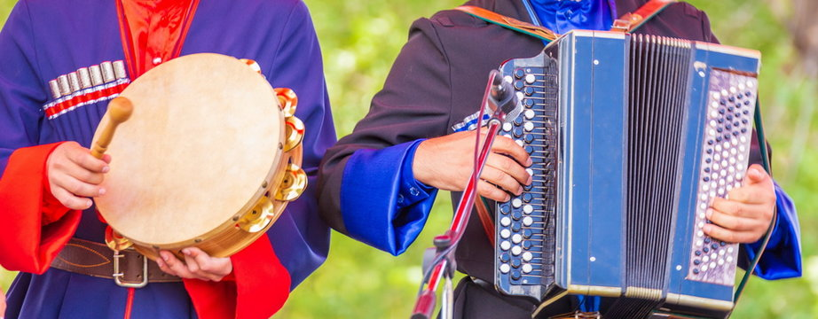 Russian harmonica with three rows and tambourine in the hands of Cossack musicians.