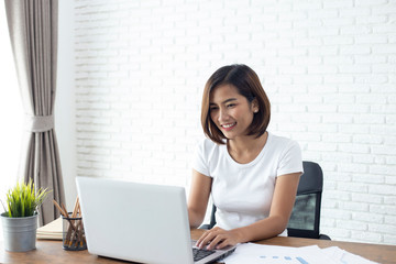 young asian woman working  laptop computer on wood desk in Home office Wall mural