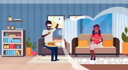 man wearing digital glasses virtual reality african american woman sitting couch eating pizza modern living room interior headset vision concept horizontal