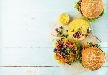 Vegetarian burger made from fresh sesame buns and raw vegetables and young sprouts blue light background.Flat layout