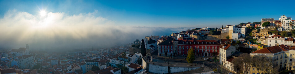 Aerial; misty morning in the ancient Alfama district of the Portuguese capital; drone view of pretty little houses, sun rising up over the clouds; natural phenomen; unusual weather in touristic area