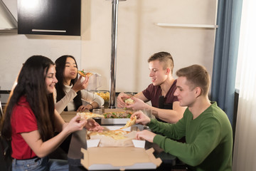Company of four young friends sitting in kitchen and taking out pizza pieces