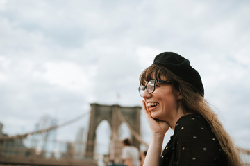 Smiling woman wearing beret with Brooklyn Bridge in background