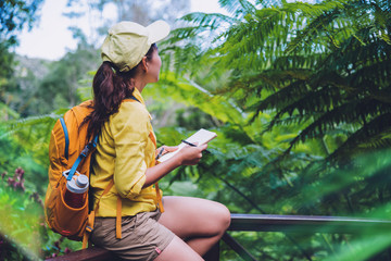 The young woman who is sitting writing, recording and studying the nature of the forest.