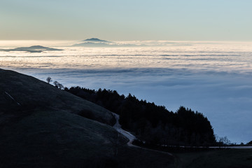 Beautiful view of Umbria valley (Italy) covered by a sea of fog at sunset, with beautiful warm colors, a mountain road and trees silhouettes in the foreground