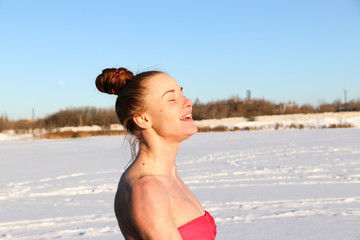 A beautiful young girl, a woman with red hair, smiles and enjoys the sun after a swim in the winter on a lake