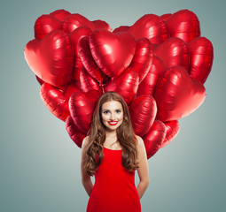 Girl in red dress with heart balloons. Beautiful woman with red lips makeup, perfect curly hair and cute smile. Surprise, valentines people and Valentine's day concept
