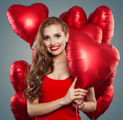 Happy woman holding balloons red heart. Surprise, valentines people and Valentine's day concept. Red lips makeup. Positive emotion.