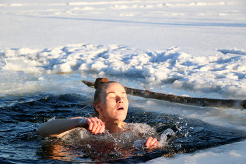 Young woman crosses herself plunging into icy water during Ukraine