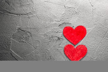 Two Red paper hearts upright on gray wall with copy space