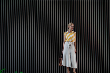 Portrait of pretty blonde woman wearing skirt and standing by the grey background.
