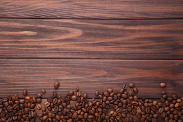 Natural coffee beans on brown wooden background