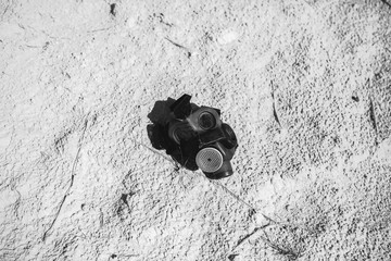 The breathing mask safety respirator is lying in the white sand at the abandoned deserted place. Environmental pollution concept. After war and post apocalyptic landscape scene.