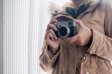 Young girl wear overcoat with holding retro camera
