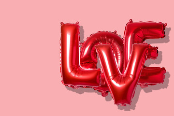 Word love in english alphabet from red balloons on a bright background. Minimal love concept.