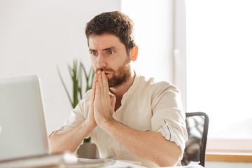 Image closeup of tense businessman 30s wearing white shirt using laptop, while working in modern office