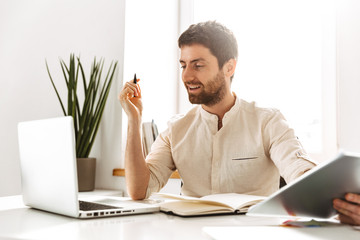 Portrait of happy businesslike man 30s wearing white shirt working with laptop and paper documents, while sitting in bright office