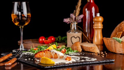 The concept of Italian cuisine. Salmon fillet with arugula, cherry tomatoes and parmesan cheese in creamy lemon sauce. A glass of white wine on the table. Dishes in the restaurant.