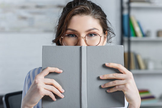 woman in glasses covering face with book in modern office